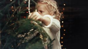 La niña adorna el árbol de navidad almacen de video