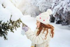 La niña adorna el árbol de navidad Imagenes de archivo