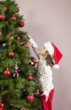 La niña adorna el árbol de Navidad con la bola roja Fotos de archivo libres de regalías