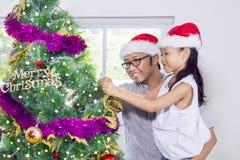 La niña adorna el árbol de navidad con su padre Foto de archivo