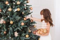 La niña adorna el árbol de navidad enorme para el celebratio del día de fiesta Imágenes de archivo libres de regalías