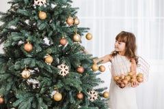 La niña adorna el árbol de navidad verde enorme Fotografía de archivo libre de regalías