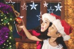 La niña adorna un árbol de abeto con la madre Fotos de archivo