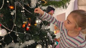 La niña adorna un árbol de navidad almacen de metraje de vídeo