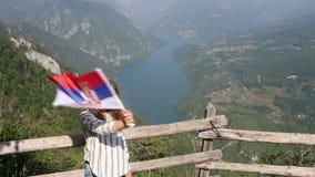 La niña agita con una bandera servia en la montaña Tara Serbia almacen de video