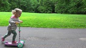 La niña agradable está montando la vespa Ocio activo en parque almacen de video
