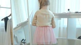 La niña alegre con las coletas en una falda rosada intenta encendido los zapatos de la madre en los talones y las danzas delante  almacen de video