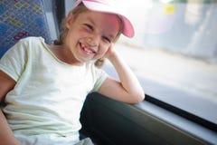 La niña alegre en una gorra de béisbol rosada va por el autobús Fotos de archivo libres de regalías