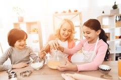 La niña alegre está batiendo los huevos en cuenco con leche y su hermano está vertiendo la harina fotografía de archivo