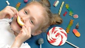La niña alegre miente en un fondo azul con los dulces Retrato del primer metrajes