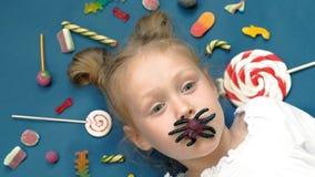 La niña alegre miente en un fondo azul con los dulces Retrato del primer almacen de metraje de vídeo