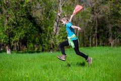 La niña alegre salta en la hierba Fotos de archivo