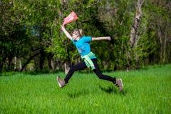 La niña alegre salta en la hierba con un paquete fotos de archivo libres de regalías