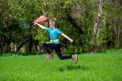 La niña alegre salta en la hierba con un paquete Imagen de archivo