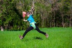 La niña alegre salta en la hierba con un paquete foto de archivo libre de regalías