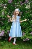 La niña alegre se está colocando en el arbusto de una lila Imagenes de archivo