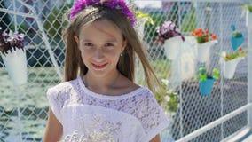 La niña apacible con las flores a disposición presenta en barra de bahía lentamente almacen de metraje de vídeo