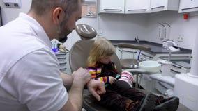 La niña aprende de dentista cómo cepillar los dientes metrajes