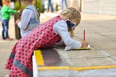 La niña aprende extraer con un lápiz en un trozo de papel de la revista de los niños en el patio de escuela imágenes de archivo libres de regalías