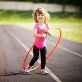 La niña aprende hacer girar el aro Imagen de archivo