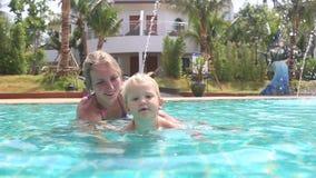 La niña aprende nadar y salpica en piscina almacen de metraje de vídeo