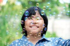 La niña asiática está sonriendo con las burbujas de jabón que flotan alrededor Fotografía de archivo