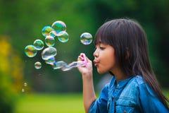La niña asiática está soplando burbujas de un jabón Imagen de archivo