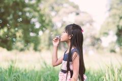 La niña asiática está soplando burbujas de un jabón en el parque Imagen de archivo