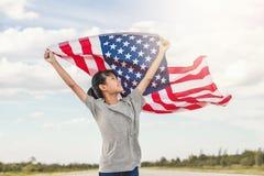 La niña asiática feliz con la bandera americana los E.E.U.U. celebra el 4 de julio imagen de archivo libre de regalías