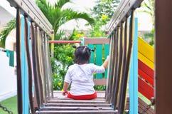 La niña asiática se sienta cómodamente en el patio Tailandia Imagenes de archivo