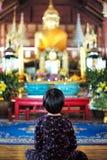 La niña asiática se sienta delante de las estatuas de oro grandes de Buda imágenes de archivo libres de regalías