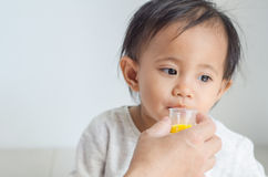 La niña asiática toma el jarabe de la medicina con su madre Foto de archivo