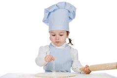 La niña asperja la harina en la pasta de la pizza foto de archivo
