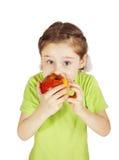 La niña asustada muerde una manzana roja grande Imagen de archivo