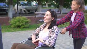 La niña ayuda a la madre a una persona discapacitada en una silla de ruedas en el paseo almacen de metraje de vídeo