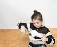 La niña bastante seria concentrada en el papel del corte adornó el corazón para el día de tarjetas del día de San Valentín Fotografía de archivo