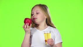 La niña bebe el jugo de un vidrio y sostiene una manzana Pantalla verde Cámara lenta metrajes