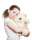 La niña bonita abraza un oso de peluche Fotografía de archivo