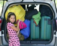 La niña bonita con los corazones viste cargas el coche de equipaje Imagen de archivo
