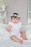 La niña bonita en un vestido blanco y con una diadema en una cabeza se sienta en una cama Foto de archivo
