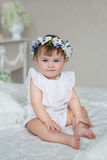 La niña bonita en un vestido blanco y con una diadema en una cabeza se sienta en una cama Imágenes de archivo libres de regalías