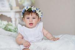 La niña bonita en un vestido blanco y con una diadema en una cabeza se sienta en una cama en un dormitorio Foto de archivo
