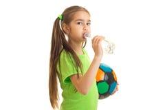 La niña bonita en uniforme del verde con el balón de fútbol bebe el agua Foto de archivo libre de regalías