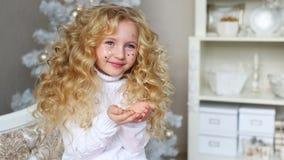 La niña bonita rizada sostiene un confeti en las manos y las sonrisas almacen de metraje de vídeo