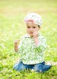 La niña bonita se está sentando en la hierba Fotos de archivo