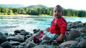 La niña bonita se está sentando en un banco del río de la montaña y está jugando con las piedras almacen de video