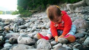 La niña bonita se está sentando en un banco del río de la montaña y está jugando con las piedras metrajes