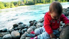 La niña bonita se está sentando en un banco del río de la montaña y está jugando con las piedras almacen de metraje de vídeo