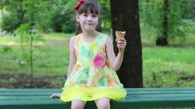 La niña bonita se sienta en banco y come el helado en el día de verano almacen de metraje de vídeo