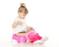 La niña bonita se sienta en el potty. imagen de archivo